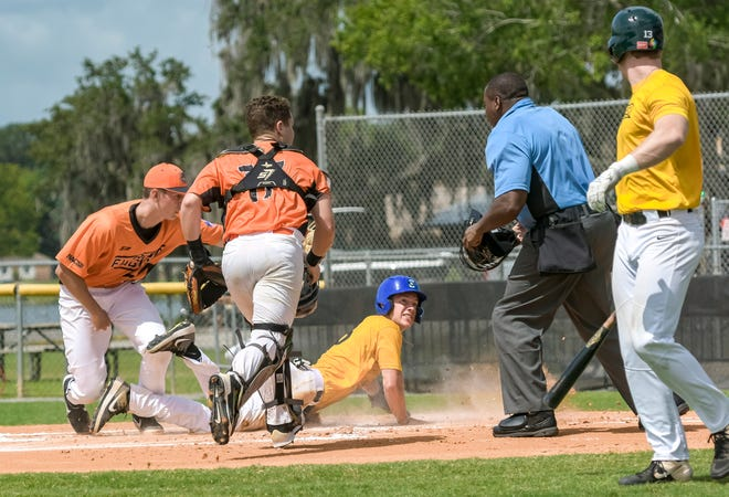 Cameron Frederick (13) of the Leesburg Storm looks to the umpire for a call after sliding home against the DeLand Suns during a 2020 game at Pat Thomas Stadium-Buddy Lowe Field in Leesburg. [PAUL RYAN / CORRESPONDENT]
