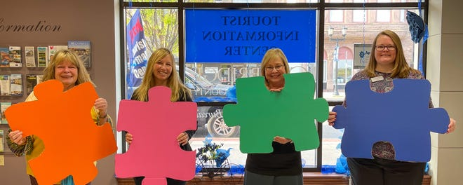 Cambridge/Guernsey County Visitors & Convention Bureau staff members, from left, Dixie Lacy, Terri Herron, Debbie Robinson and Karen Castello hold large puzzle pieces to advertise an activity to mark National Travel andTourism Week.