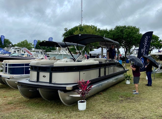 Larry Gardner of Jacksonville Marine points out the features of this Barletta Ultra Entertainer pontoon boat to two visitors using umbrellas on a soggy Sunday afternoon at the Jacksonville Spring Boat Show at Metropolitan Park and Marina.