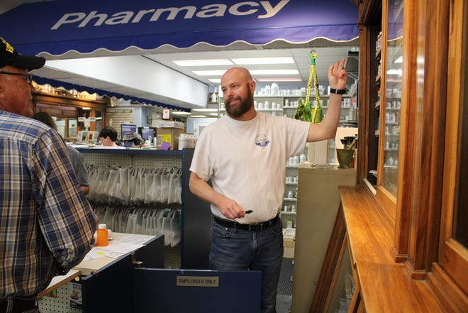 Central Drug of Bessemer City owner Robby Putnam (right) speaks to longtime customer and former employee Paul Bullard at the store on Wednesday, April 21, 2021.