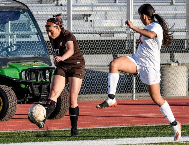 Garden City High School's Anahi Castillo, left, moves the ball upfield past Great Bend's Yulisa Valdez during a Western Athletic Conference matchup April 8 at Buffalo Stadium. The Buffaloes defeated the Panthers 8-0 Tuesday at Great Bend.