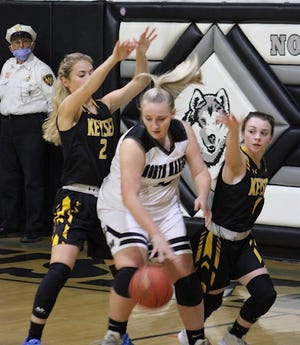 Keyser's Maddy Broadwater and Maddie Harvey surround their North Marion opponent.