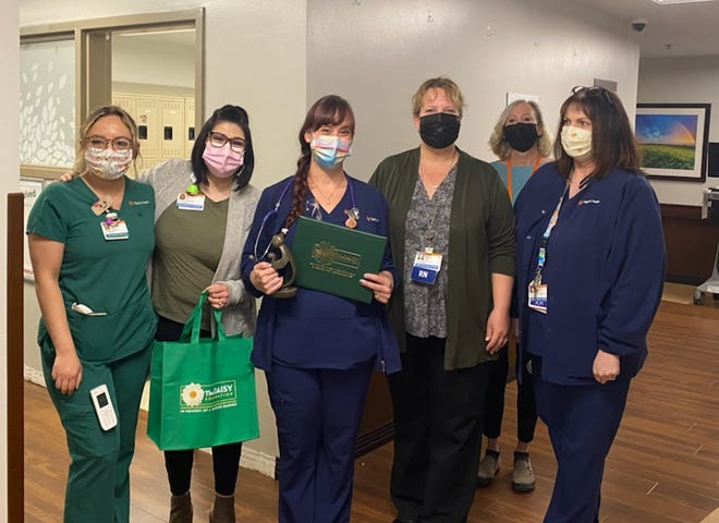 RN Alexis Najera, third from left and holding an award, was the recipient of the DAISY Award last week. The award recognizes nurses who go above and beyond in their work.