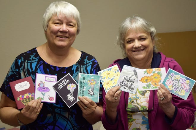 Joyce Scarbough and Kat Abbott hold up cards they handcrafted for the Cards for Soldiers project.  Each week they spend four hours crafting cards for the military overseas to send back to their families.
