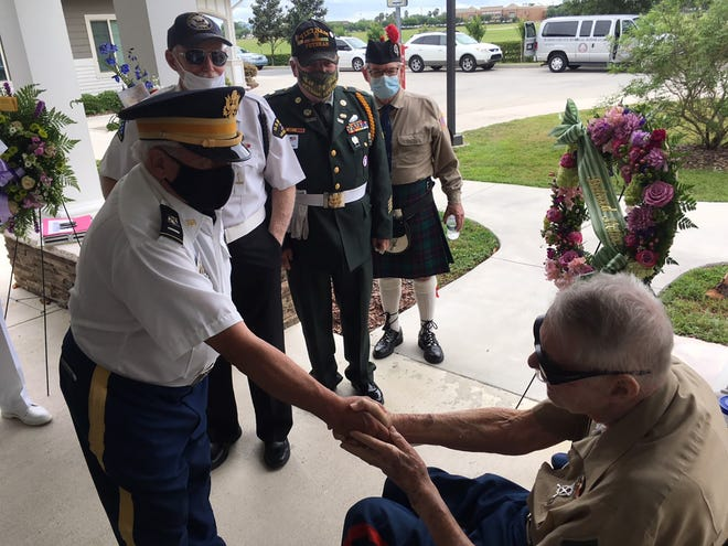 Edward Harrison, right, is greeted last week during a special ceremony honoring his late wife, Patricia, who died last month.