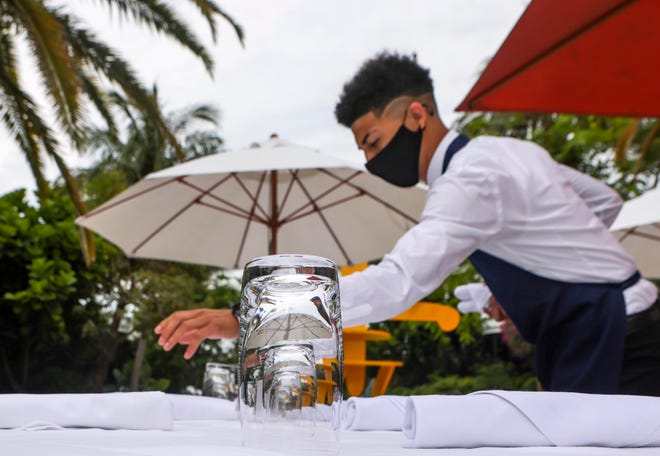 Josh Garcia, 22, a busser at Sant Ambroeus Palm Beach, arranges silverware on tables in the restaurant's outside patio dining area just prior to lunch on Wednesday.