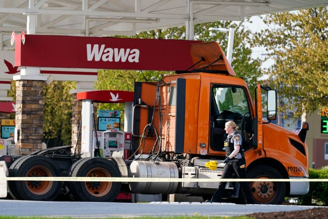 "An investigator works the crime scene at a Wawa convenience store and gas station in Breinigsville, Pa., Wednesday, April 21, 2021. Police on Wednesday converged on a convenience store in eastern Pennsylvania following what state police called a ""serious police incident"" that has closed several businesses and a school. (AP Photo/Matt Rourke)"
