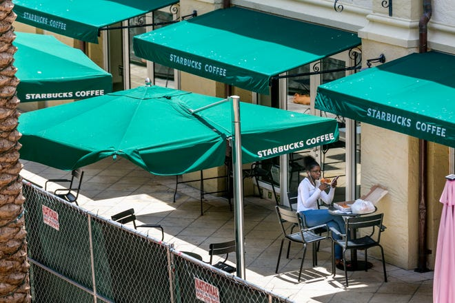 A person eats outside the Starbucks during renovations at Rosemary Square in West Palm Beach, Florida on July 25, 2019. [GREG LOVETT/palmbeachpost.com]