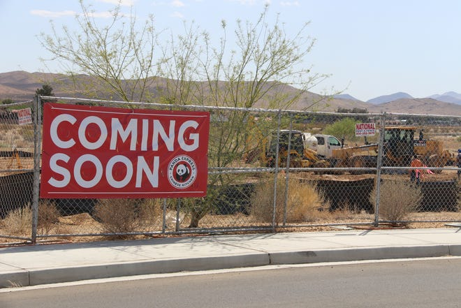 """Construction workers and equipment can be glimpsed through a fence on April 21, 2021 building a new Panda Express restaurant near the Ridgecrest Walmart Supercenter. The restaurant chain serves """"American Chinese food"""" according to its website."""
