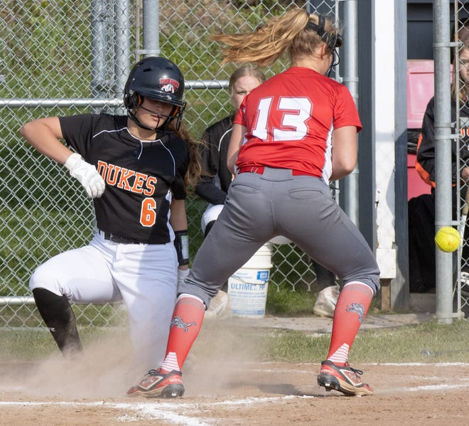Marlington's Ava Collins is safe at home plate in front of Minerva's Bella Murray during Thursday's game. (Special to The Canton Repository / Bob Rossiter)