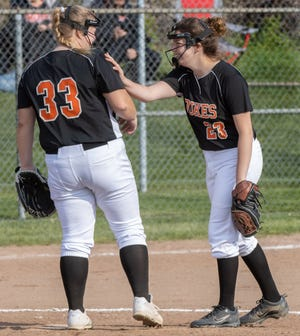 Marlington's Ashlyn Maurer (33) and Sofia Nase (23) talk between innings during their game at Minerva on Tuesday, April 20, 2021. (Special to The Canton Repository / Bob Rossiter)