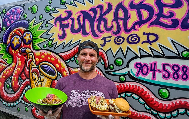 Jerry Asker, the owner of Funkadelic food truck, holds plates of his food in front of his trailer in the Marina Munch food truck park on U.S. 1 in St. Augustine on Tuesday, April 20, 2021.