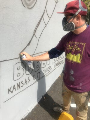 Scott Nurkin paints what will become the Bobby Bell mural in Shelby.