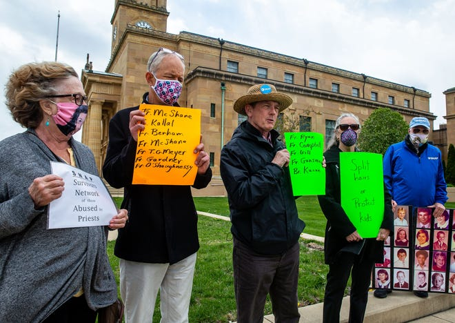 "David Clohessy, center, holds up a sign with the names of five priests accused of abuse as members of the Survivors Network of those Abused by Priests, SNAP, gather to urge Bishop Thomas John Paprocki to include the names on the diocese's list of ""credibly accused"" priests during a protest at the Cathedral of the Immaculate Conception in Springfield, Ill., Wednesday, April 21, 2021. [Justin L. Fowler/The State Journal-Register]"