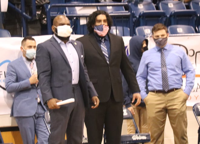 Shawnee wrestling coach Nik Turner (front, left) and his coaching staff observe a match during the 2020-21 season.
