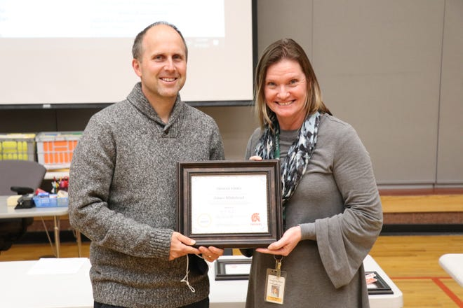 """Music teacher Jim Whitehead was recognized as a """"Trojan Hero"""" for his work with students. Assistant superintendent Nicole Airgood presented each recipient with a plaque."""
