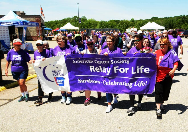 Cancer survivors carry a banner and march with other survivors and supporters at the annual American Cancer Society Relay for Life at Dodd Stadium in Norwich June 8, 2019. [John Shishmanian/ NorwichBulletin.com]