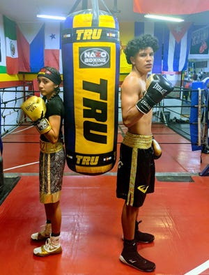 Iveth, left and Isaac Alvarez, right, pose in Gil Trujillo's home boxing gym during a workout. The two have already won multiple national championships in their respective amateur careers.