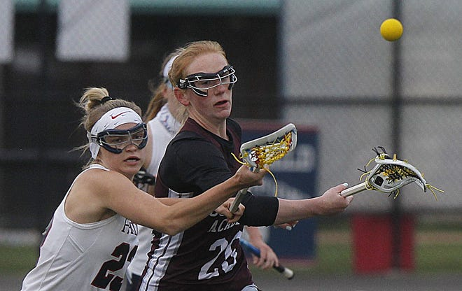 Columbus Academy senior midfielder Charlotte Adams battles Hartley's Sydney Onega (left) during the Vikings' 14-10 win April 15. Adams had seven goals and one assist in Academy's first six games.
