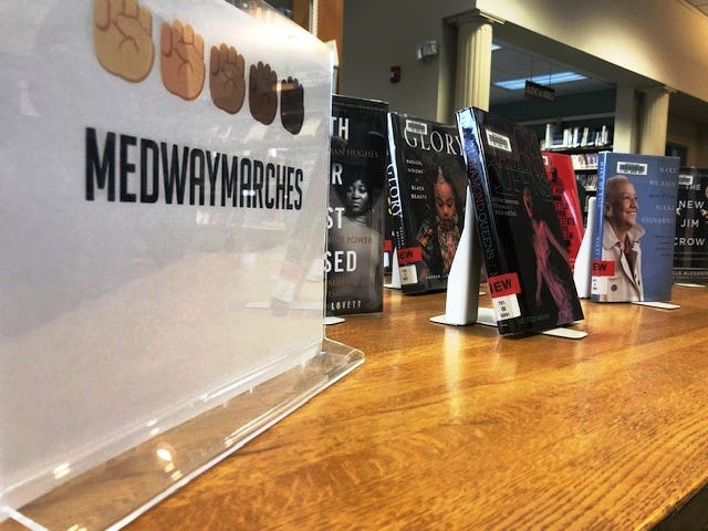 Medway Marches donated money raised from selling lawn signs so the Medway Library could expand its offerings written by and related to people of color. Many of the books are currently on display and available to borrow.