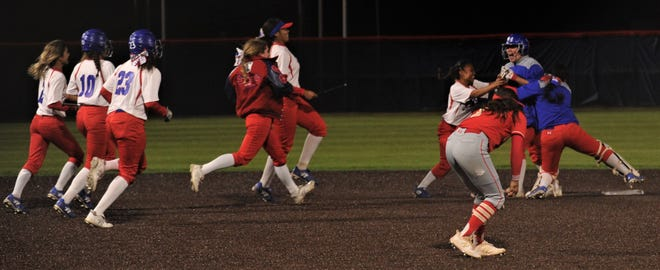 Cooper players race to congratulate Jayden Falcon, near left, after Falcon's two-run double in the seventh inning lifted the Lady Cougars to a 9-8 victory over Lubbock Coronado.
