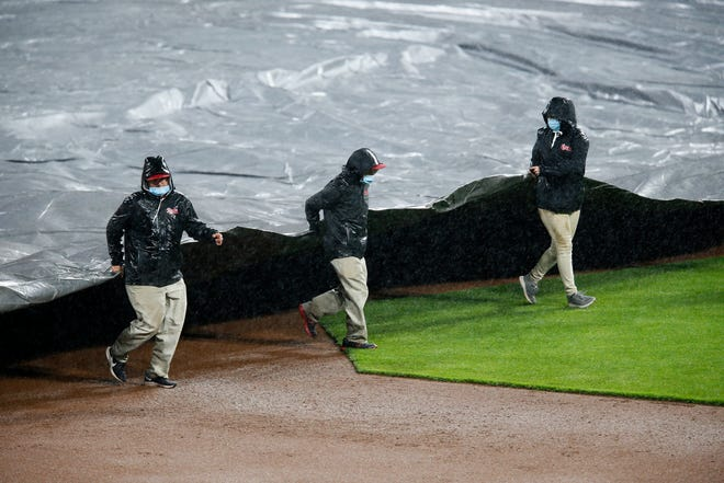 The grounds crew pulls the tarp as the game enters a rain delay in the eighth inning of the MLB National League game between the Cincinnati Reds and the Arizona Diamondbacks at Great American Ball Park in downtown Cincinnati on Tuesday, April 20, 2021. The game entered a rain delayed after Cincinnati Reds starting pitcher Lucas Sims (39) walked in the go-ahead run in the top of the eighth and refused throw any more pitches in the heavy rain.