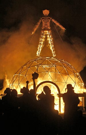 In this Sept. 4, 2004 file photo the crowd of thousands cheer as the Burning Man is burned to the ground, at the 18th annual Burning Man Celebration, at Black Rock Desert.