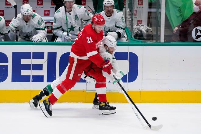 Defenseman Detroit Red Wings Dennis Cholowski (21) dan center Dallas Stars Joe Pavelski (16) bersaing untuk mendapatkan puck pada babak pertama pertandingan hoki NHL di Dallas, Selasa, 20 April 2021.