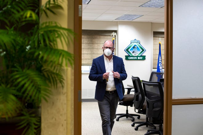Green Bay Mayor Eric Genrich walks out of his office to go to a press conference on April 21.