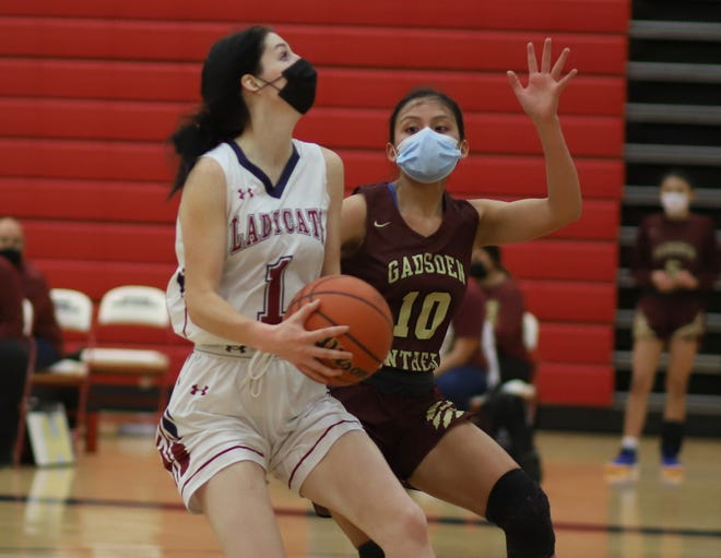 Senior Lady 'Cat Sierra Manos (1) put Panther players on her hip en route to the basket Tuesday. Manos pumped in a career-high 29 points to lead the Deming High Lady Wildcats to a 65-37 victory.