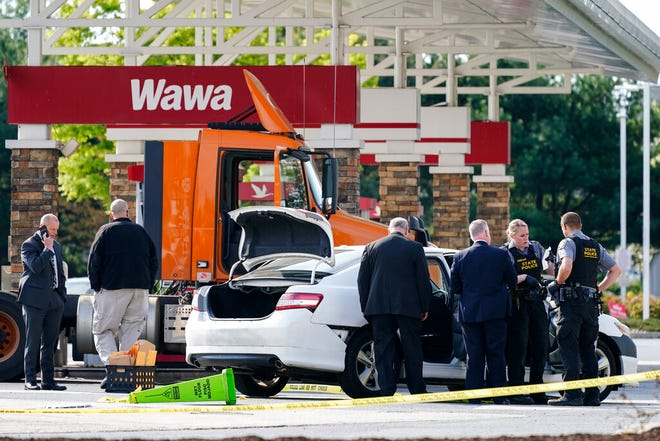 """Crime investigators work the scene at a Wawa convenience store and gas station in Breinigsville, Pa., Wednesday, April 21, 2021. Police on Wednesday converged on the convenience store in eastern Pennsylvania following what state police called a """"serious police incident"""" that has closed several businesses and a school. (AP Photo/Matt Rourke)"""