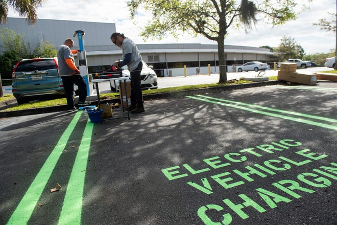 Electric Avenue workers Steve Huskey (left) and Carlos DeJesus (right) install two Level 2 electric vehicle charging stations with four ports Monday, March 8, 2021, at the TCPalm and Treasure Coast Newspapers printing press and newsroom in Port St. Lucie. TCPalm partnered with Florida Power & Light Co. to help expand charging ports across the state.