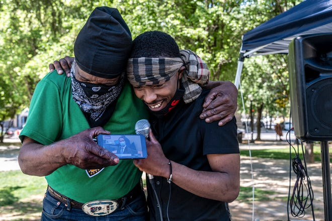 Stevante Clark, right, brother of Stephon Clark who was fatally shot by Sacramento Police, is hugged by his cousin Steven Ray Collins, left, at Cesar Chavez Park in Sacramento, California Tuesday as they listen live to the guilty verdict of former Minneapolis police Officer Derek Chauvin for the murder of George Floyd. A jury convicted Chauvin on murder and manslaughter charges.