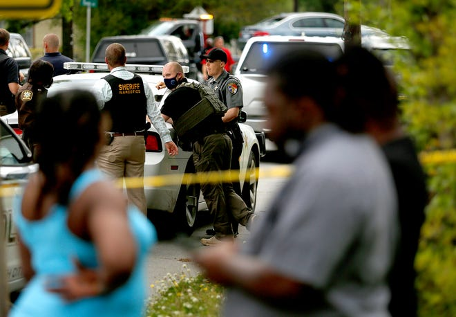 Law enforcement investigate the scene of a fatal police shooting on Wednesday.