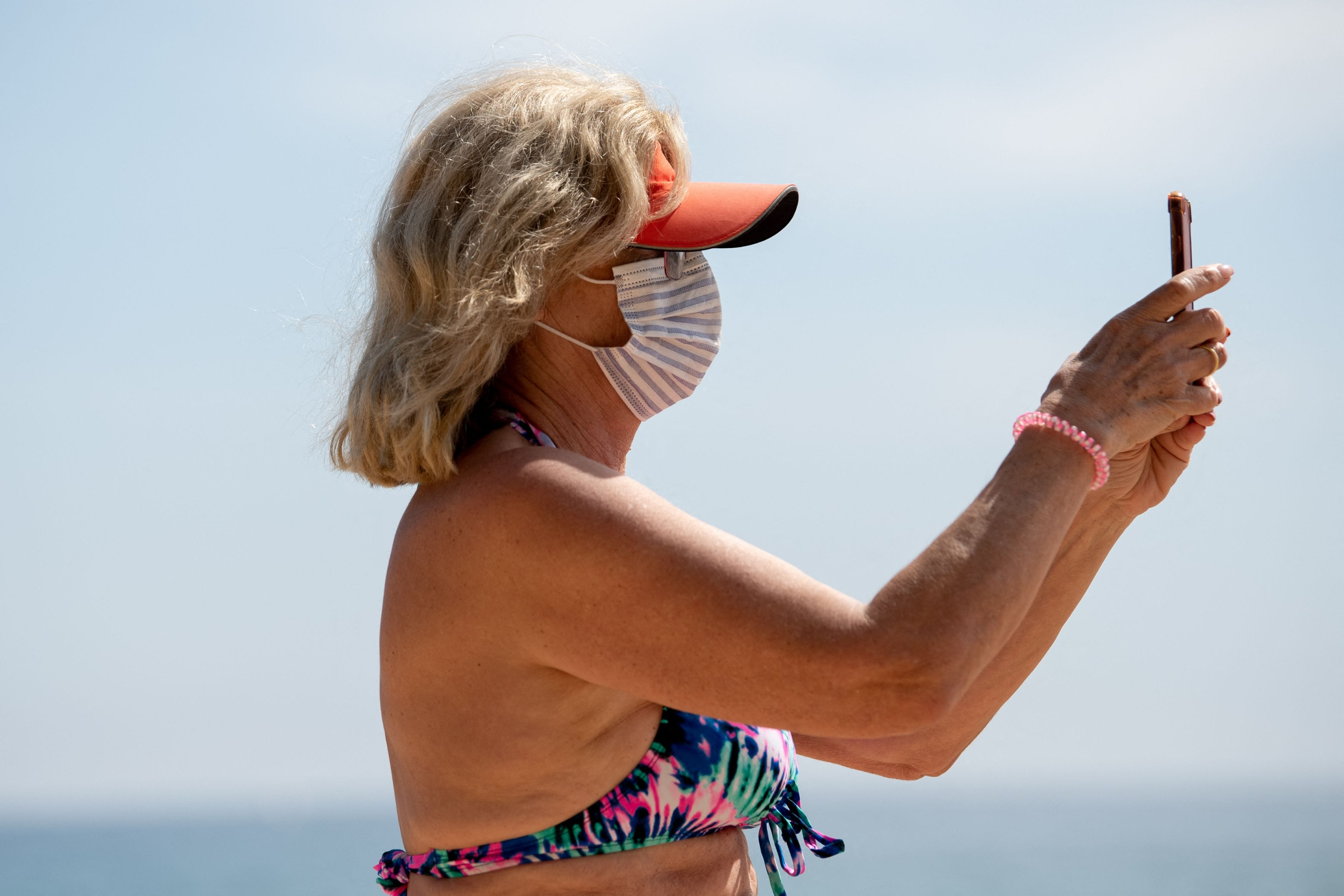 A woman wearing a face mask uses her smartphone on Sa Conca Beach in Castell-Platja D'Aro near to Girona, Spain, on March 31, 2021.