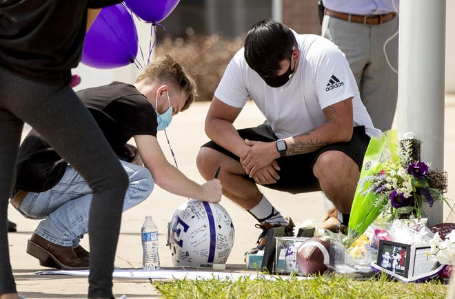 Friends gather at a memorial for two slain students at Elgin High School on Monday, April 19. Authorities on Monday arrested 41-year-old Stephen Broderick and charged him with killing his wife, daughter and another teen.  [JAY JANNER/AUSTIN AMERICAN-STATESMAN via AP]