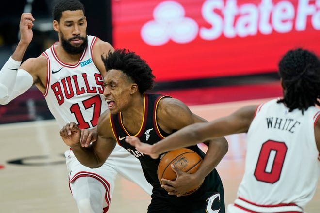 Cavaliers guard Collin Sexton, center, drives between Chicago Bulls' Garrett Temple, left, and Coby White during the Cavs' 121-105 win Wednesday night.  [Tony Dejak/Associated Press]