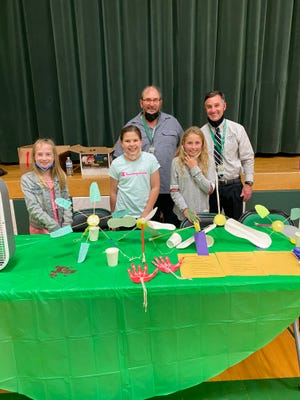 West Branch Intermediate students Charlee Campbell, from left, Aislyn Ring and Tenley Stitle stand with teacher Scott Hesley, left, and Principal Fritz Schlueter to share their projects of wind cars, McGuyver wind lift and prosthetic hand.
