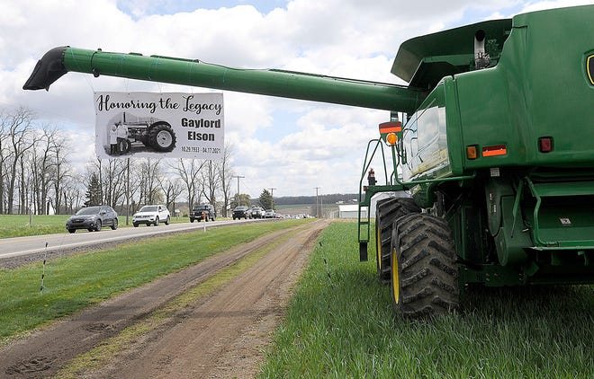 The funeral procession for local farmer Gaylord Elson drives past his tractors lined up in front of his farm on state Route 302 on Thursday, April 22, 2021. TOM E. PUSKAR/TIMES-GAZETTE.COM
