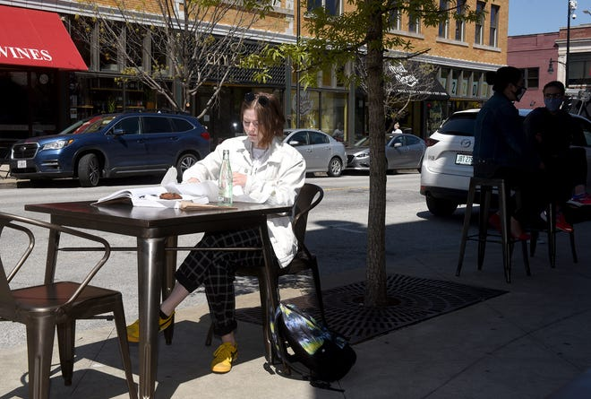 """Nikki Reijmer, a junior at the University of Missouri, prepares to eat her lunch Thursday in front of the Strollway Market at 114 S. Ninth St. The Columbia City Council voted in favor of a """"Restaurant Right of Way"""" ordinance allowing downtown restaurants to use parking spaces to serve diners in front of their restaurants."""
