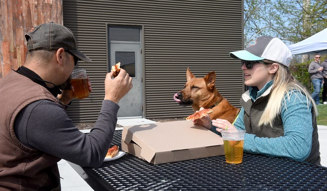 Rodney and Laura Moon enjoy pizza and beer with their dog Pretzel, 7, during the Earth Day celebration in April at Logboat Brewing Company, 504 Fay St. The brewery is an independent entity in what is being called the Arcade District by a developer. This is an area of north-central Columbia that runs along Fay Street from Wilkes Boulevard to Rogers Street and is bordered by Columbia College and North College Avenue.