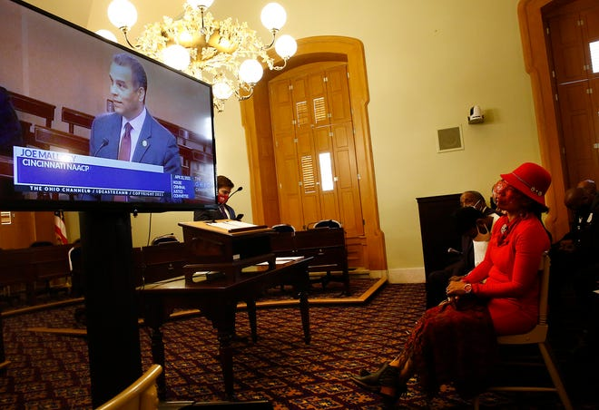 Rev. Pamela M. Pinkney Butts, of Cleveland, right, listens as the president of the Cincinnati NAACP, Joe Mallory, on the tv monitor, expresses opposition to House Bill 22 disagrees during a committee hearing at the Ohio Statehouse on Thursday, April 22, 2021.