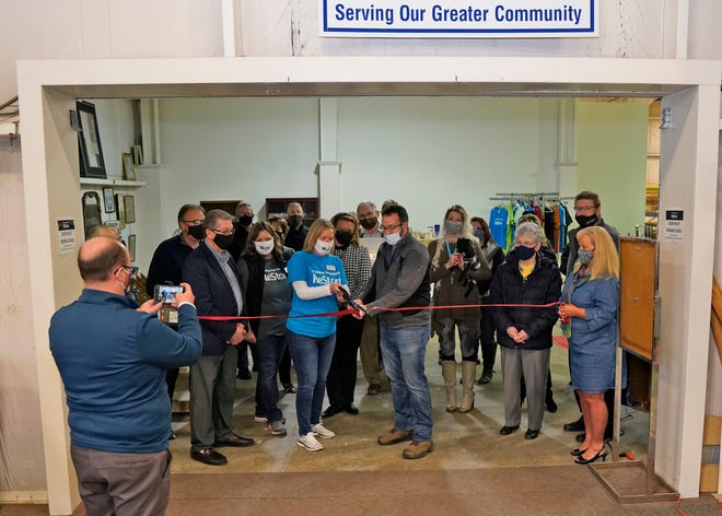 Habitat for Humanity of Lenawee County executive director Wendy Knox, left center, and ReStore director Anthony Sacco cut the ceremonial ribbon Tuesday at the opening of the expanded ReStore in Madison Township.