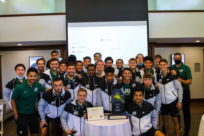 Members of the Jacksonville University soccer team display their ASUN championship trophy earlier this week during the team gathering for the NCAA selection show.