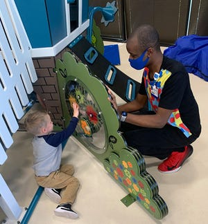 Rehab tech Ricardo Foster interacts with a child at Wolfson Children's Hospital's Autism and Neurodevelopment Center. He has autism and has become a role model for the young patients he works with.