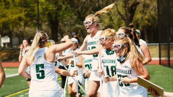 The Jacksonville University women's lacrosse team celebrates its 12-11 victory over Florida on March 13.