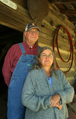 Rodney and Lynn Willis pose outside their restored log cabin at Willis Farms in Belwood Thursday morning, April 22, 2021.