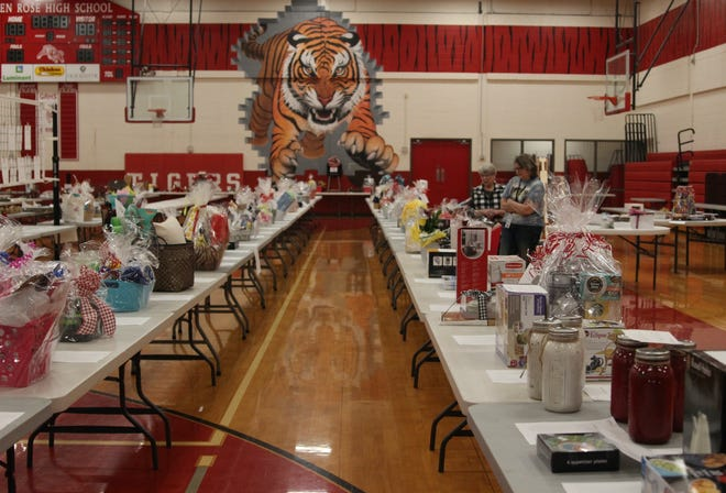 Tables filled with items for a silent auction line the Red Gym at Glen Rose High School as part of Project Graduation.