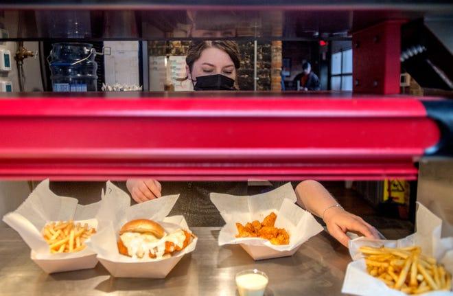 Maquet's Rail House server Melissa Petitt picks up food orders for her lunch customers Wednesday, April 21, 2021 at the popular Pekin restaurant.