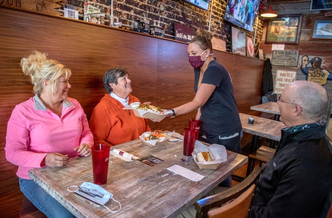 Kami Ferguson serves up fare Wednesday, April 21, 2021 to Michelle Johnson, left, Jeff Roth, right, and Tammy Smith at Maquet's Rail House, 221 Court Street, in Pekin.